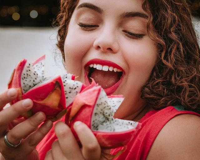 Obézna žena, ktorá je sladké ovocie