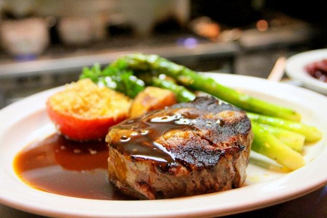 Steak so zeleninou a omáčkou naložený na tanieri.jpg