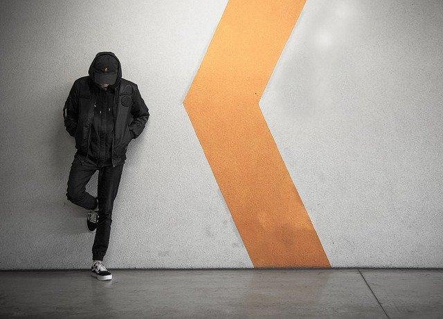 Muž v čiernej bunde stojí opretý o stenu.jpg