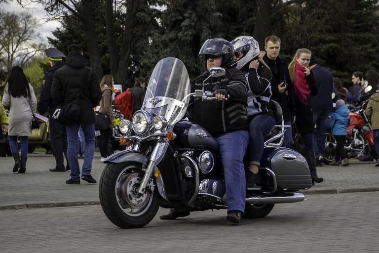 Muž so ženou na motorke, dav ľudí, mesto