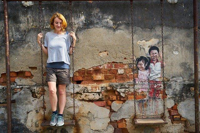 Usmiata žena stojí na hojdačke pri stene s grafitmi.jpg