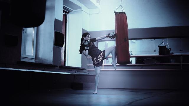 Žena s holými nohami kope do boxovacieho mechu.jpg